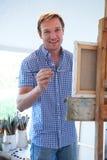 Artista de sexo masculino Painting In Studio Imagen de archivo libre de regalías
