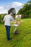 Artista de sexo masculino solo que trabaja al aire libre en el parque o el jardín Fotografía de archivo