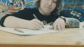 Artista de Tattooer que crea la imagen para el cliente almacen de metraje de vídeo