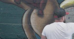 Artista dei graffiti con la bottiglia dello spruzzo di aerosol video d archivio
