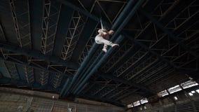 Artista del circo sulle cinghie dell'antenna nella grande costruzione abbandonata stock footage