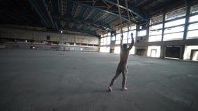 Artista del circo sulle cinghie dell'antenna nella grande costruzione abbandonata archivi video