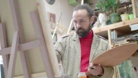 Artista del hombre en imagen de la pintura del delantal en lona en estudio del arte metrajes