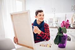 Artista del hombre joven que pinta en casa la pintura creativa fotos de archivo
