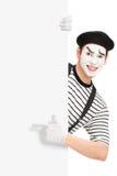Artista del mimo che indica su un pannello in bianco Immagine Stock Libera da Diritti