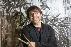Artista del pittore che posa davanti alla pittura immagine stock