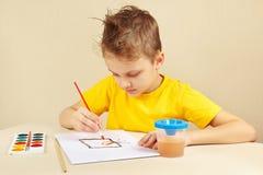 Artista del principiante en la pintura amarilla de la camisa con las acuarelas Fotos de archivo