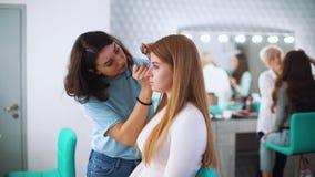 Artista del salón de belleza que hace el maquillaje profesional para el cliente femenino joven almacen de video