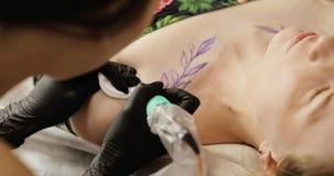 Artista del tatuaggio che fa tatuaggio con le foglie allo studio per la giovane donna, primo piano archivi video