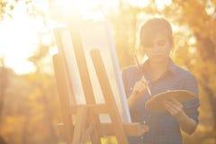 Artista della giovane donna che disegna un'immagine su tela su un cavalletto nella natura, in una ragazza con una spazzola ed in  fotografie stock libere da diritti