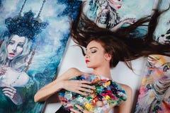 Artista desnudo de sexo femenino hermoso rodeado por la lona de pinturas en el fondo del blanco del piso Cepillos y gama de color Foto de archivo libre de regalías