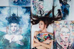 Artista desnudo de sexo femenino hermoso rodeado por la lona de pinturas en el fondo del blanco del piso Cepillos y gama de color Imagen de archivo