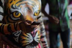 Artista di ballo della tigre che per mezzo del telefono cellulare fotografia stock libera da diritti