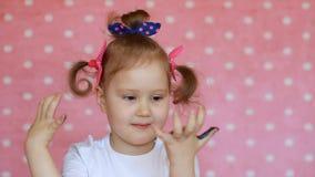 Artista divertente del bambino con le palme sporche in pittura Bambina felice con le mani dipinte variopinte con i sorrisi su un  archivi video
