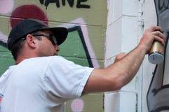 Artista dos grafittis no trabalho na pintura mural Imagem de Stock