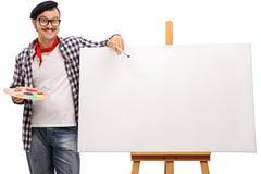 Artista eccentrico che posa accanto ad una tela immagini stock