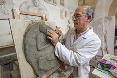 Artista en el estudio del arte en el trabajo sobre una escultura de arcilla stock de ilustración