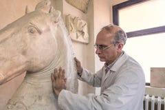 Artista en el estudio del arte en el trabajo sobre una escultura de la cabeza de caballo grande de la arcilla libre illustration