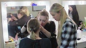 Artista, estudiante y modelo de maquillaje El proceso de aprendizaje Blonde joven Las cejas del dibujo del artista de maquillaje  almacen de metraje de vídeo