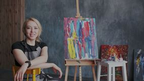 Artista fêmea louro bonito inspirado que senta-se em seu local de trabalho Sorri e olhando na câmera moderno filme