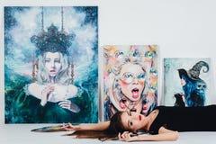 Artista fêmea na lona da imagem no fundo branco Pintor da menina com escovas e paleta Conceito da criação da arte Fotografia de Stock Royalty Free