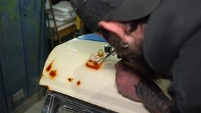 Artista farpado adulto do retrato na pintura do tampão que focaliza com o aerógrafo na capa do carro filme