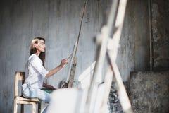 Artista femminile con i pennelli e la tavolozza in sue mani che dipingono nello studio Fotografia Stock
