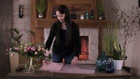 Artista floral de la mujer profesional, florista que corta el documento de embalaje sobre la tabla para el ramo en el taller, est almacen de metraje de vídeo