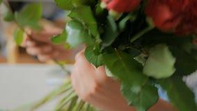 Artista floral profesional que trabaja con las flores en el estudio metrajes