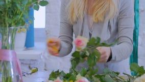 Artista floral profesional que trabaja con las flores en el estudio almacen de video