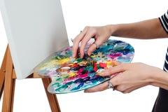 Artista hermoso lindo de la muchacha que pinta una imagen en el caballete de la lona Espacio para el texto Fondo blanco del estud Foto de archivo