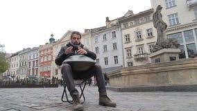 Artista joven de la calle que se realiza en la calle El ejecutante con handpan o cuelga que sea un musical étnico tradicional del almacen de video