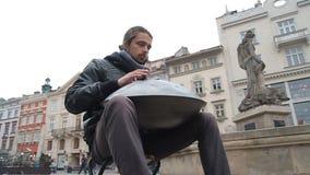 Artista joven de la calle que se realiza en la calle El ejecutante con handpan o cuelga que sea un musical étnico tradicional del metrajes