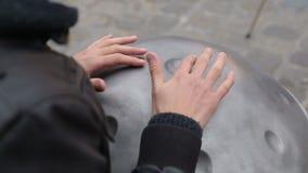 Artista joven de la calle que se realiza en la calle El ejecutante con handpan o cuelga que sea un musical étnico tradicional del almacen de metraje de vídeo