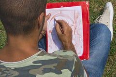 Artista joven mientras que dibuja Fotografía de archivo libre de regalías