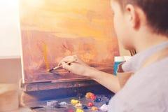 Artista joven que dibuja la imagen abstracta en estudio Imagen de archivo libre de regalías