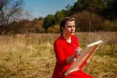 Artista joven que pinta un paisaje foto de archivo