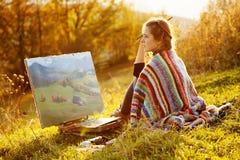 Artista joven que pinta un paisaje del otoño