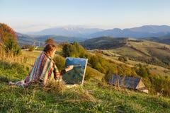 Artista joven que pinta un paisaje del otoño fotos de archivo