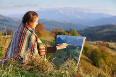Artista joven que pinta un paisaje del otoño imagenes de archivo
