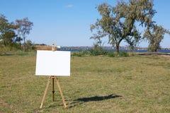 Artista joven que pinta un paisaje del otoño en el fondo de la naturaleza Concepto del arte fotografía de archivo