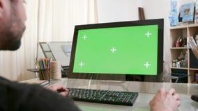 Artista joven que trabaja en su ordenador con la pantalla verde en la exhibición almacen de metraje de vídeo