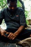 artista local que cinzela uma estátua tribal de madeira pequena na areia vulcânica preta na praia tropical do oceano do mar imagens de stock royalty free