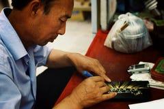 artista local que prepara uma parte gravada da arte em sua oficina foto de stock