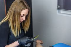 Artista louro que fotografa a tatuagem que lhe está fazendo clien Imagens de Stock Royalty Free