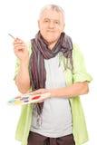 Artista maduro que sostiene una plataforma del color y una brocha Fotografía de archivo