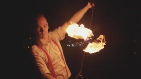Artista maschio che esegue manifestazione del fuoco al buio al rallentatore video d archivio