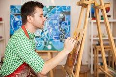 Artista maschio che lavora una pittura Immagine Stock