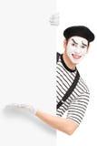Artista maschio sorridente del mimo che mostra su un pannello Immagine Stock Libera da Diritti