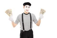 Artista maschio sorridente del mimo che tiene i dollari americani ed esame del camer Fotografia Stock